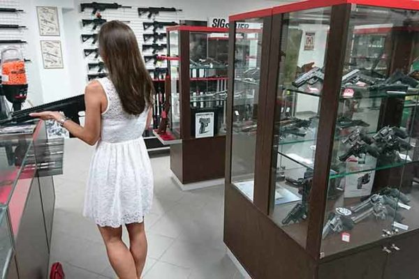 Woman Buying First Gun in Gun Store
