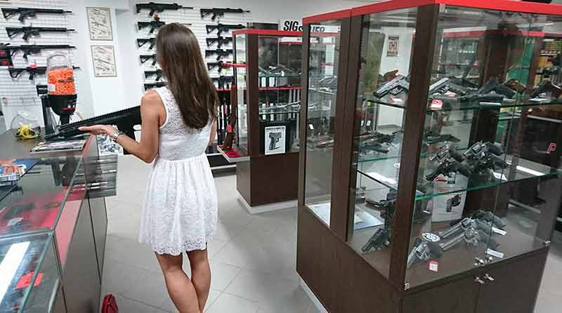 Woman Buying First Gun in Gun Store